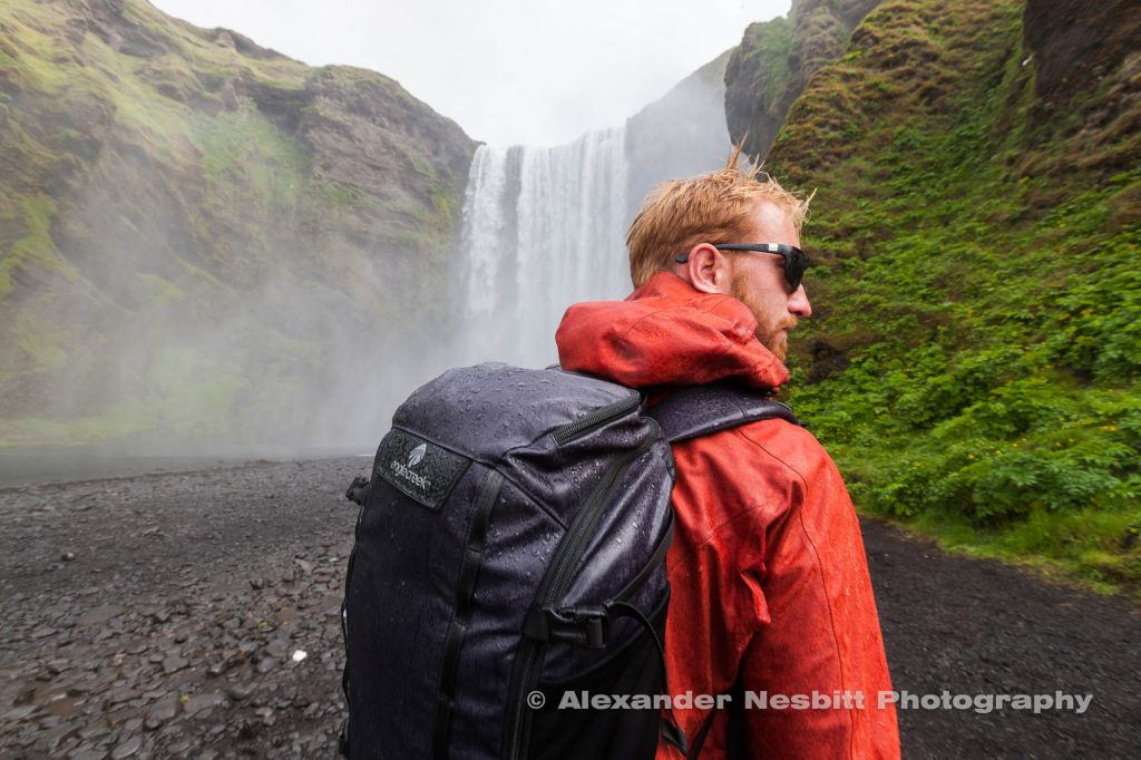 Photo by Alexander Nesbitt shot for Eagle Creek, shows a young man wearing a backpack next to a waterfall in Iceland