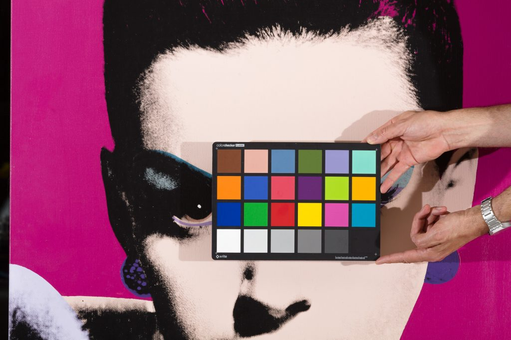 Image of a Xrite color checker in front of an artwork being photographed for reproduction